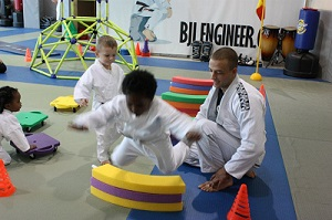 Coach Joe helping mini ninja jump at naples jiu jitsu class.